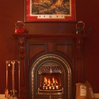 Valor Portrait series gas fireplace with a coal basket, Windsor arch with chrome highlights and Fires of Tradition mantel.